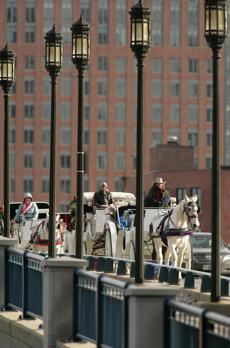 Horse-drawn carriages from the Bridal Carriage Company crossed the Seaport Boulevard bridge, which is paved, on their way to the Faneuil Hall area.